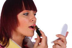 Red-haired woman applying lipstick, isolated. Red-haired woman with a mirror, applying lipstick, isolated on white Stock Photography