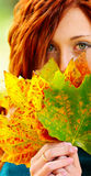 Red haired woman and autumn leaves Royalty Free Stock Photos