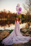 Red-haired woman with balloons in her hand and in a fairy purple dress at sunset. Red-haired woman with balloons in her hand and in a fairy purple dress is Royalty Free Stock Photography