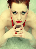 Red haired woman in bath Stock Photos