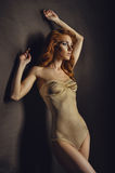 Red haired woman in beige bodysuit Royalty Free Stock Images