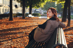 Red haired woman on a bench Royalty Free Stock Images