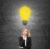 Red haired woman and a big light bulb Stock Image