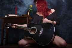 Red haired woman and the black acoustic guitar Royalty Free Stock Photo