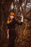 Red-haired woman in black dress dark forest, dry Stock Images
