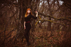 Red-haired woman in black dress dark forest, dry Royalty Free Stock Images
