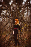 Red-haired woman black dress in dark forest, dry Royalty Free Stock Photography