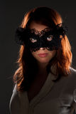 Red-haired woman in a black mask. Mysterious photograph of a girl in a mask royalty free stock images