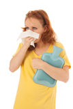 Red haired woman blowing nose with hot water-bottle. Red haired woman with yellow shirt blowing nose while holding hot water bottle isolated over white Stock Images