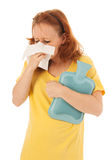 Red haired woman blowing nose with hot water-bottle Royalty Free Stock Image