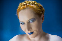 Red-haired woman with blue lips. Blue-eyed red-haired woman with blue lips on a blue background Stock Photography