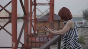 Red-haired woman by the bridge chatting online and smileing. Red-haired woman by the bridge with headphones, chatting oline and smileing, hipster style, outdoor stock video