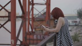 Red-haired woman by the bridge chatting online. Red-haired woman by the bridge with headphones, chatting oline, hipster style, outdoor portrait on the embankment stock video
