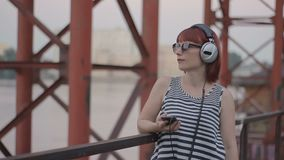 Red-haired woman by the bridge listening music in earphones. Red-haired woman by the bridge wear headphones, listening music in earphones, hipster style, outdoor stock video