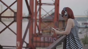 Red-haired woman by the bridge chatting and listening music in earphones. Red-haired woman by the bridge wear headphones, chatting and listening music in stock video footage