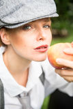 Red-haired woman with cap in the garden bites in an apple Royalty Free Stock Photo