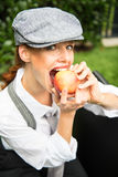Red-haired woman with cap in the garden bites in an apple Royalty Free Stock Photos