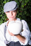 Red-haired woman with cap in the garden offers apple Stock Image