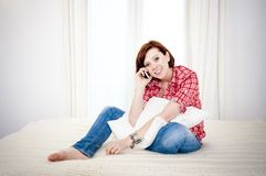 Red haired woman on couch talking on mobile cell. Red haired business woman or student on couch or bed happy on her mobile cell phone wearing a red shirt on a Royalty Free Stock Images