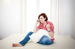 Red haired woman on couch talking on mobile cell Royalty Free Stock Image