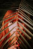 Red Haired-woman Covered by Green Leaf stock photos