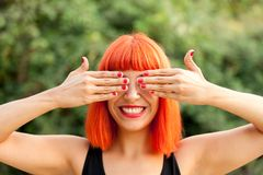 Red haired woman covering her eyes in a park Stock Photo