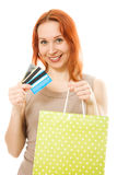Red-haired woman with credit cards and shopping. Red-haired woman with many different credit cards and shopping isolated on white Royalty Free Stock Photos