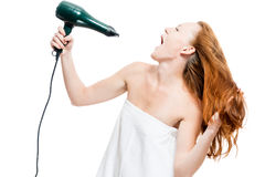 Red-haired woman dries hair with a hairdryer on a white Royalty Free Stock Photo