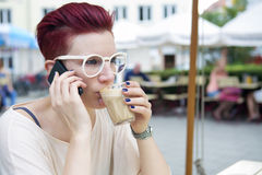 Red-haired woman drinking coffee and talking on the phone Royalty Free Stock Photo