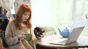 Red haired woman drinking tea and using her phone in a cafe. Beautiful red haired woman is sitting in a cafe and drinking tea from a large green mug. Laptop in stock footage
