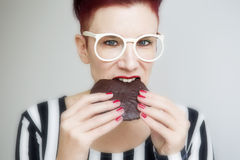 Red-haired woman eating a big chocolate cookie Stock Photo