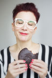 Red-haired woman eating a big chocolate cookie Royalty Free Stock Images