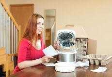 Red haired woman with electric crock pot in her kitchen at home Stock Photos