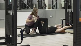Sports red-haired woman is engaged in the gym with an individual trainer. Sport, rehabilitation, health. The red-haired woman is engaged in the gym with an stock footage