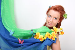 Red-haired woman with flowers and butterflies Royalty Free Stock Image