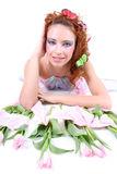 Red-haired woman with flowers lying Stock Images