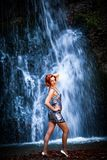 Red-haired woman in front of a waterfall royalty free stock image