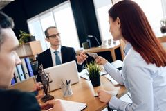 Red-haired woman gives money to lawyer for divorce, sitting at office table. stock photography