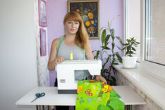 A red-haired woman and her sewing machine. Love your working place Stock Image