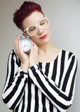 Red-haired woman holding alarm clock with her eyes closed Stock Photo