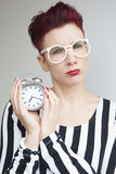 Red-haired woman holding alarm clock looking upset Royalty Free Stock Photos