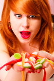 Red haired woman holding candies in hands. stock photo