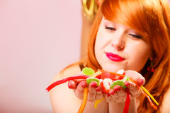 Red haired woman holding candies in hands. stock photography