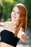 Red haired woman holds thumb up Royalty Free Stock Image