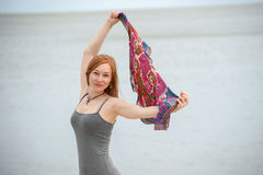Red-haired woman holds up a shawl Royalty Free Stock Photography