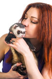 Red haired woman kissing ferret Royalty Free Stock Photo