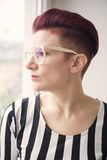 Red-haired woman looking through window Royalty Free Stock Images