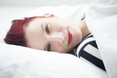 Red-haired woman lying in bed Royalty Free Stock Photo
