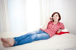Red haired woman lying down on couch talking on mobile cell Royalty Free Stock Photography