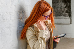 Red haired woman with mobile device near wall Royalty Free Stock Image